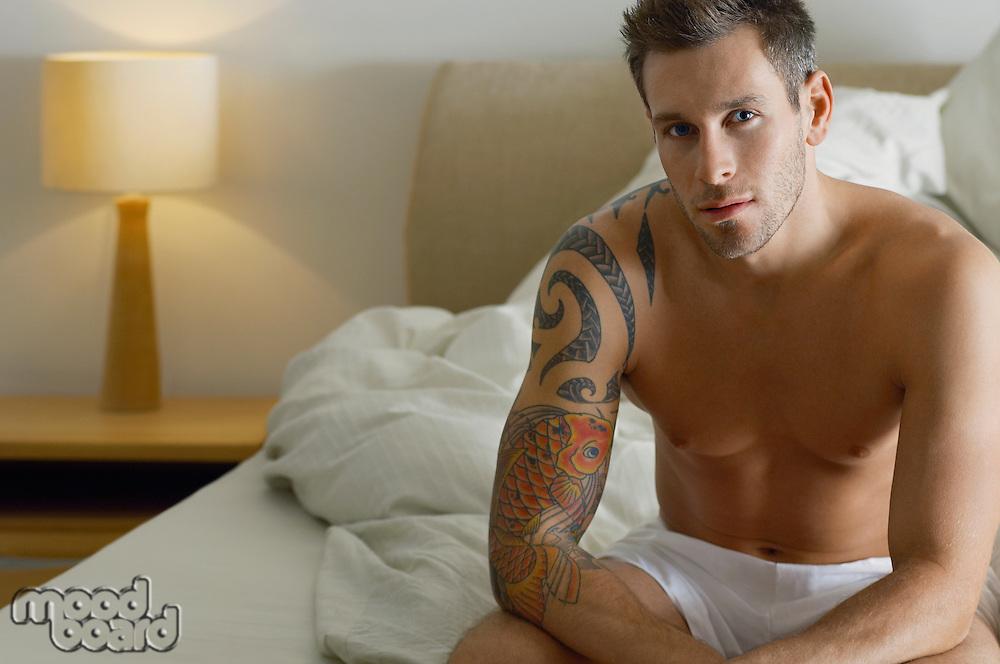 Shirtless Man Sitting on Bed