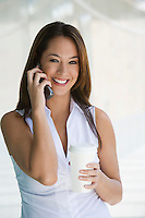 Woman using cell phone holding takeout coffee, portrait