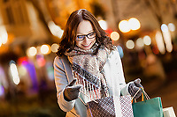 Portrait of young attractive woman smiling while looking at her new clothes on paper bag