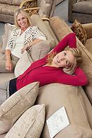 Portrait of daughter relaxing on sofa while mother looking in furniture store