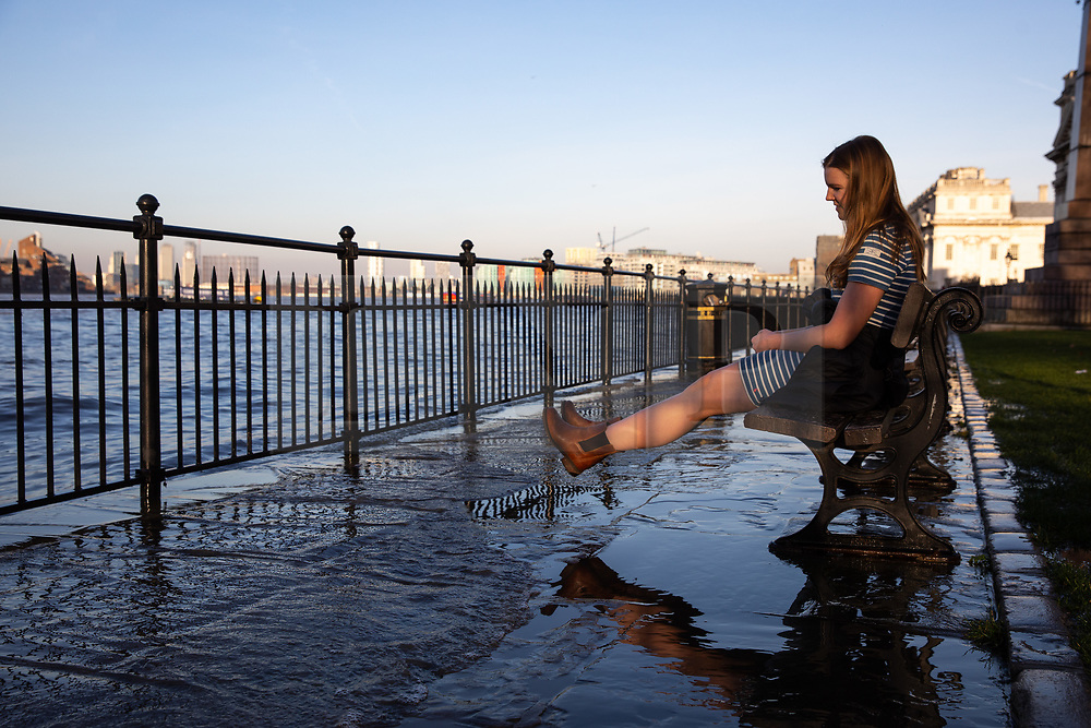 © Licensed to London News Pictures. 22/02/2019. London, UK. A woman sits on a bench in Greenwich as an extreme high tide causes the River Thames to flood onto the Thames Path. The weather is also unseasonably warm in the capital, with temperatures set to reach 16 degrees Celsius this weekend. Photo credit : Tom Nicholson/LNP