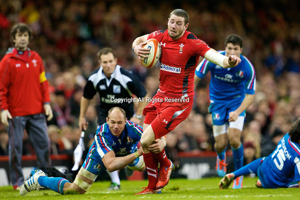 01.02.2014 Cardiff, Wales. Wales wing Alex Cuthbert (Cardiff Blues) and Italy number 8 Sergio Parisse (Stade Français) during the Six Nations game between Wales and Italy from the Millennium Stadium.