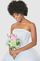 Beautiful African American bride holding bouquet over gray background