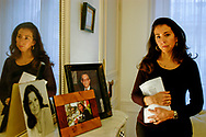 Astrid Betancourt, sister of the French-Colombian politician Ingrid Betancourt who has been held captive by the FARC marxist guerrillas in the Colombian jungle since February 23, 2002, in her Paris apartment next to photos of her parents and her sister. She is holding a 12 page letter written by Ingrid that was recently recovered by Colombian authorities along with video tapes. It was the first proof that Ingrid Betancourt was still alive that the family has received since May 2003.<br /> Paris, France. 11/12/2007