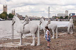 "© Licensed to London News Pictures. 02/09/2015 London, UK. A girl looks at the art installation entitled ""The Rising Tide"" (comprising four horse-riders on horses with petroleum pumps for heads) by the underwater eco-sculptor Jason deCaires Taylor, which stands on the foreshore of the River Thames in Vauxhall and is revealed with each low tide.  The installation aims to question man's reliance on fossil fuels and is part of this year's Totally Thames festival. Photo credit : Stephen Chung/LNP"