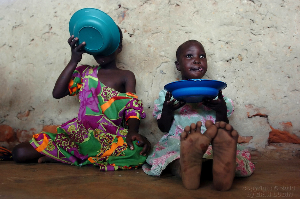 Children sip on bowls of porridge for lunch while in day care at Coope Camp in Gulu District, north Uganda, on October 6, 2006. Coope Camp, with a population of approximately 18,000, is one of 76 camps outside the town of Gulu created for internally displaced people in north Uganda. Since the war began in 1987  over 2 million people have moved from their village homes to camps close to the town of Gulu where they can be protected from the LRA, the Lord's Resistance Army, by the UPDF, the Ugandan People's Defense Force. Over the years the LRA are said to have abducted more than 30,000 children for use as soldiers in their army. The children were often tortured and girls were frequently used as sex slaves. Current peace talks between the Ugandan government and the LRA taking place in Juba, southern Sudan, have the north Ugandan community hoping for an end to the 20 year long war..Photo by Erin Lubin