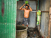 05 SEPTEMBER 2013 - BANGKOK, THAILAND:  A Cambodian worker bathes in a corrugated metal outhouse after their construction shift at the construction site of a new high rise apartment / condominium building on Soi 22 Sukhumvit Rd in Bangkok. The workers live in the corrugated metal dorms on the site. Most of the workers at the site are Cambodian immigrants.             PHOTO BY JACK KURTZ