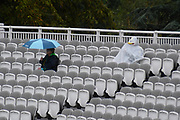 A couple of spectators sheltering from the heavy rain in different ways in the Compton Stand ahead of the International Test Match 2019 match between England and Australia at Lord's Cricket Ground, St John's Wood, United Kingdom on 18 August 2019.