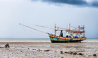 Grounded Fishing Boat: A solitary grounded fishing boat at low tide and apparently abandoned, seen in profile before an approaching storm, in Ko Lanta - Thailand.