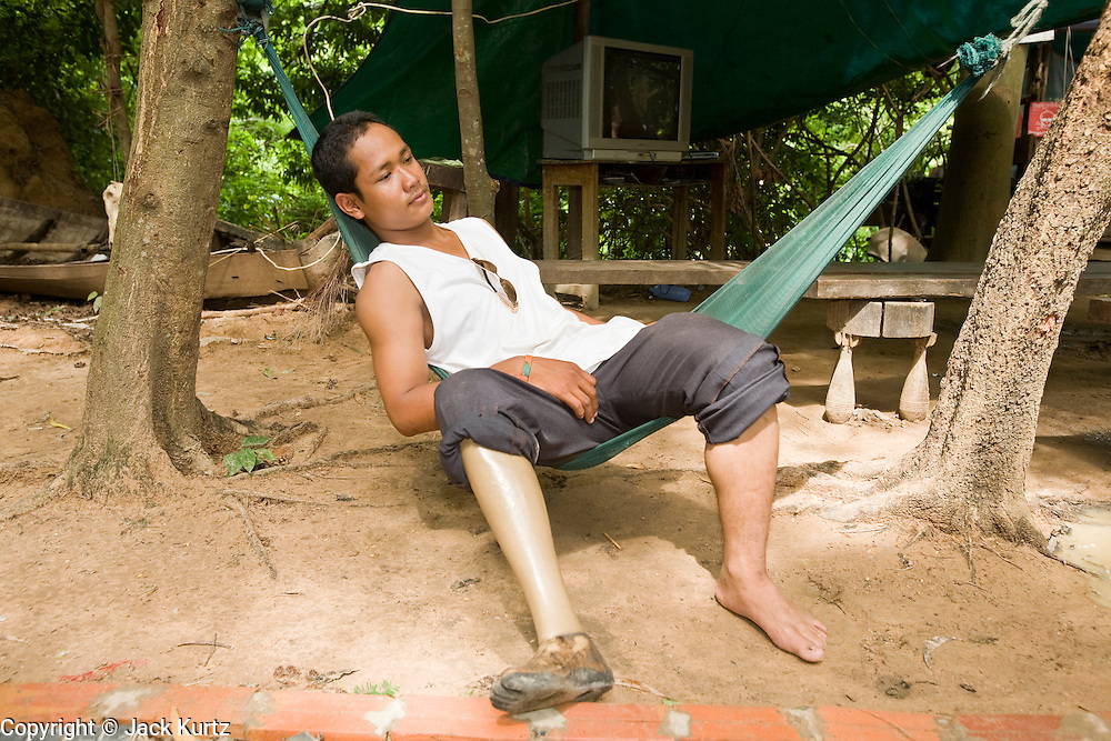 26 JUNE 2006 - SIEM REAP, CAMBODIA: HOOT NAK, 19, rests in a hammock at the landmine museum operated by Cambodian anti-landmine activist Aki Ra in Siem Reap, Cambodia. Hoot was nine years old when he was walking through a rice paddy with his brother and sister. He stepped on a small plastic mine that took off his foot and killed his brother and sister. Cambodians are still wrestling with the legacy of the war in Vietnam and subsequent civil wars. At one time it was the most heavily mined country in the world and a vast swath of Cambodia, along the Thai-Cambodian border, is still mined. In 2004, more than 800 people were killed by mines and unexploded ordinance still found in the countryside.  Photo by Jack Kurtz