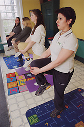 Women taking part in aerobics exercise class in women only homeless hostel,
