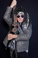 Portrait of senior male heavy rock metal guitarist over black background