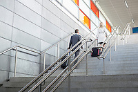 Rear view of businessman and businesswoman with luggage moving upstairs in railroad station
