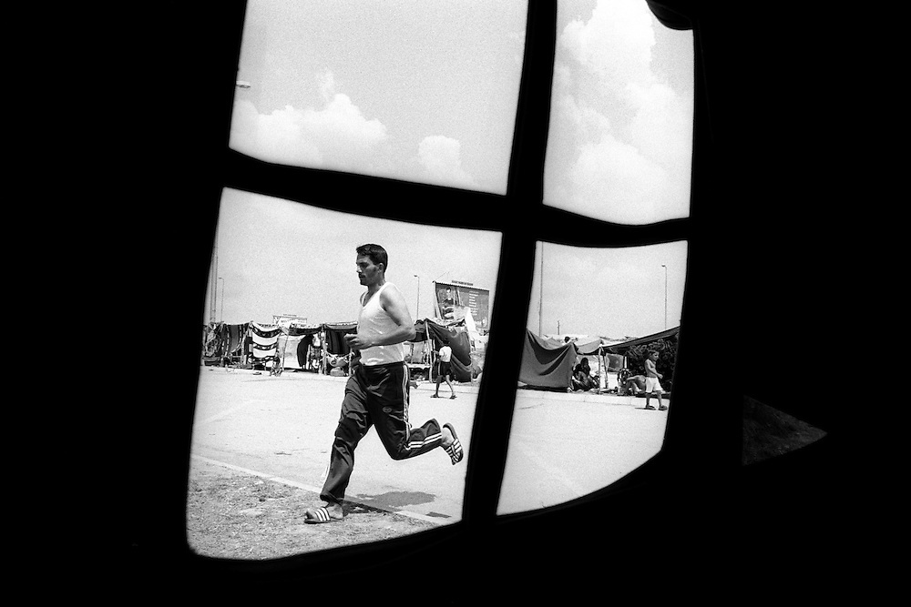 One of the young Roma men runs past the medical tent, where a team of nurses from nearby town came every day. In the background you can see the makeshift camp build by the refugees from bits of tree and plastic sheets. .In May 2003, 700 Roma refugees from Kosovo ? currently in Macedonia - attempted to cross into Greece, but failed. Turned back by riot police they decided to stay on the border to highlight their plight. After 3 months they gave up and returned back to Skopje, Macedonia's capital...Medzitlija, Greek - Macedonian border.