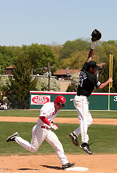 18 April 2010:Matt Mirabal outruns the throw from the other side of the field when it is thrown high and Chris Serritella has to jump to stop it.  Southern Illinois Salukis and the Illinois State Redbirds face off on Duffy Bass Field on the campus of Illinois State University in Normal Illinois.