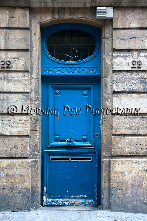 A blue door with graffiti from a building in Paris, France.