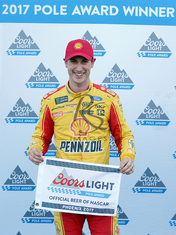 Joey Logano poses for the media after winning the pole for Sunday's NASCAR Cup Series auto race on Friday, March 17, 2017, in Avondale, Ariz.  (AP Photo/Rick Scuteri)