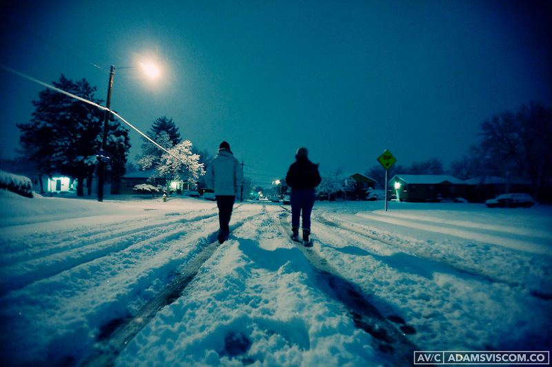Two people walk along a snow covered street in Denver, CO.