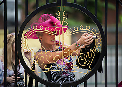 © London News Pictures. 20/06/2013. Ascot, UK.  A woman attempts to photograph a celebrity from outside the security gates at Ladies Day on day three of Royal Ascot at Ascot racecourse in Berkshire, on June 20, 2013.  The 5 day showcase event,  which is one of the highlights of the racing calendar, has been held at the famous Berkshire course since 1711 and tradition is a hallmark of the meeting. Top hats and tails remain compulsory in parts of the course. Photo credit should read: Ben Cawthra/LNP