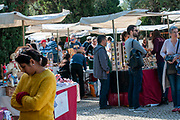 Visitors examine souvenirs and craft pieces on sale in an arts and crafts market in Belem, Lisbon, Portugal