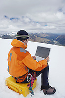 Hiker using laptop on snowy mountain peak back view