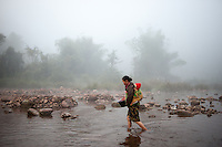 A woman walks with her child into the river for a morning bath in a northern Laotian village