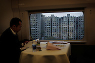 A man commutes on the fast train from Tianjing to  Beijing, China, Wednesday, Oct. 29, 2008. Block after city block, towers of concrete, steel and glass fill the skyline teeming and congested, the intensely urban landscapes of China's biggest cities show a glimpse of what the future will hold for the rest of the country. In the sprawling megacities of Beijing, Shanghai and Chongqing, where populations exceed 10 million people, extreme urban density means that the number of people living within a few square blocks here is equal to the population of entire mid-size U.S. cities. China's urban population soared to 607 million people last year _ nearly equaling the 700 million living in the countryside. The country's headlong plunge toward urbanization continues unabated as tens of millions of migrants from the countryside flood to cities in search of money, jobs and other opportunities.