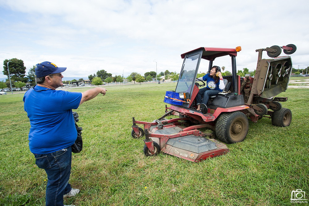 Spangler Elementary School principal Catherine Waslif takes the MUSD workhorse mower for a spin with the supervision of MUSD Bus Driver and Grounds Keeper Anthony Gomez during the California School Employees Association Appreciating Classified Employees event throughout the Milpitas Unified School District in Milpitas, California, on May 21, 2015. (Stan Olszewski/SOSKIphoto)