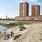"""Nederland Rotterdam 30-05-2009 20090530 Foto: David Rozing ..Nieuwbouw woningen in probleemwijk Katendrecht, kinderen spelen op het strandje aan de rivier de maas, op de achtergrond de nieuwbouw woningen, euromast. Stedelijke vernieuwing, moderne ruime wijk, natuur, natuurlijke oevers, waterveiligheid, ruimte, ruimtelijkheid, kindvriendelijk, speelplaats, speelplek, strand, speelruimte, kindvriendelijke omgeving, buiten spelen, allochtoon, allochtone, kind, jeugd, jongen, fiets, unieke locatie, stads,  New houses / appartments in (former) deprived area / projects """"Katendrecht """" This area is on a list with projects which need help of the government because of degradation in the area etc.youth, beach, children playing outside, project, suburb, suburbian, problem. Neighboorhood, neighboorhoods, district, city, problems,  daily life Holland, The Netherlands, dutch, Pays Bas, Europe ..Foto: David Rozinge"""