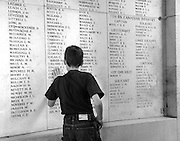 Boy reflecting upon the names of the missing on the Menin Gate, Ypres (Ieper) Belgium.