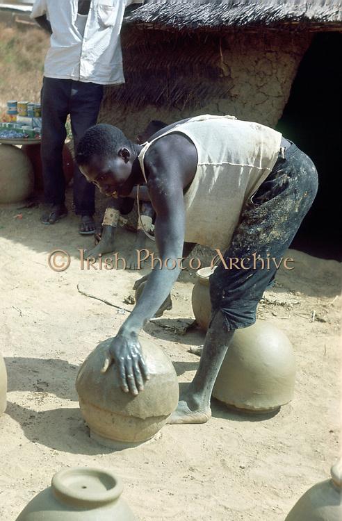 Making pots without a wheel. Nigeria c1966. Portrait format