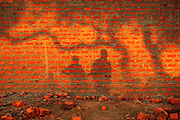 12-03-29   -- BARLONYO, UGANDA --  The setting sun projects shadows against a newly constructed brick wall in the Barlonyo trading centre on March 29. Barlonyo Camp is known primarily as the site of the 'Barlonyo Massacre' of February 21, 2004 when approximately 300 residents were killed when rebels torched the camp. Approximately 11,000 people lived in the camp, which is now a thriving trading centre and tourist attraction due to the mass grave memorial.   Photo by Daniel Hayduk