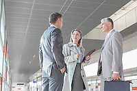 Businesswoman communicating with male colleagues on train platform