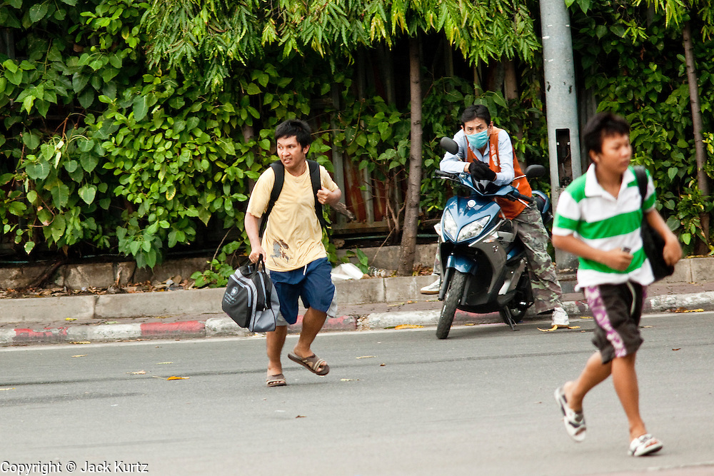 16 MAY 2010 - BANGKOK, THAILAND: People trying to evacuate their neighborhood run as sniper fire is heard along Rama IV Road in Bangkok. It's not clear who the snipers are, but the fire has been directed at anti government positions. Thai troops and anti government protesters clashed on Rama IV Road again Sunday afternoon in a series of running battles. Troops fired into the air and unidentified snipers shot at pedestrians on the sidewalks. At one point Sunday the government said it was going to impose a curfew only to rescind the announcement hours later. The situation in Bangkok continues to deteriorate as protests spread beyond the area of the Red Shirts stage at Ratchaprasong Intersection. Many protests now involve people who have not been active in the Red Shirt protests and live in the vicinity of Khlong Toei slum and Rama IV Road. Red Shirt leaders have called for a cease fire, but the government indicated that it is going to go ahead with operations to isolate the Red Shirt camp and clear the streets.      PHOTO BY JACK KURTZ