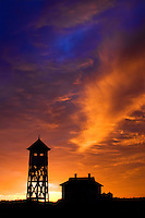 Washwoods Coast Guard Station stands in silhoutte to a dramaticaly lit sky at sunset
