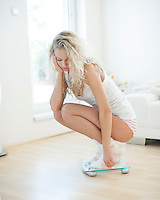 Sad young woman crouching on weighing scale