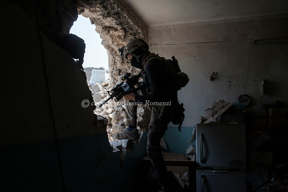 IRAQ, Mosul: An Iraqi special forces soldier passes through a hole in a house at the frontline with ISIS inside the old city in Mosul. Alessio Romenzi