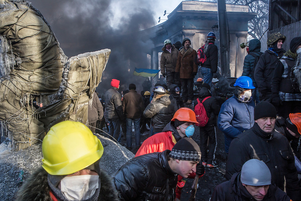 KIEV, UKRAINE - JANUARY 25: Anti-government protesters watch as others throw rocks at police during clashes on Hrushevskoho Street near Dynamo stadium on January 25, 2014 in Kiev, Ukraine. After two months of primarily peaceful anti-government protests in the city center, new laws meant to end the protest movement have sparked violent clashes in recent days. (Photo by Brendan Hoffman/Getty Images) *** Local Caption ***