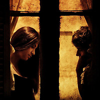 A young couple facing each other behind a window