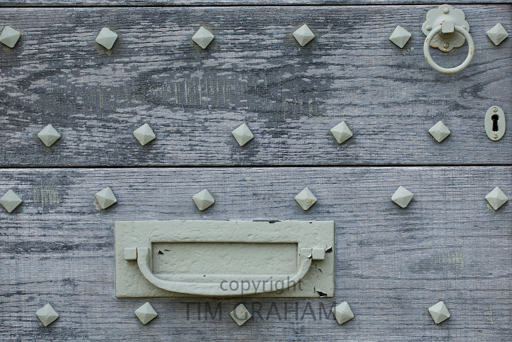 Studded front door of traditional Cotswold cottage near Southrop in The Cotswolds, Gloucestershire, UK