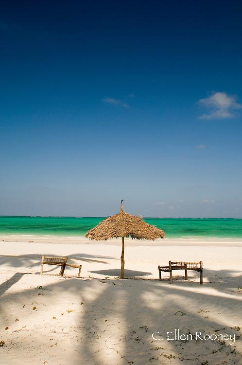 A thatched umbrella a tradtional coconut wood sunbeds on Paje Beach.  Paje, Zanzibar, Tanzania