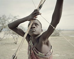 October 3, 2018 - Lake Eyasi, Ngorongoro district, Tanzania - Manu (14) shoots an arrow.The Hadza are one of the last remaining societies, which remain in the world, that survive purely from hunting and gathering. Very little has changed in the way the Hadza live their lives. But it has become increasingly harder for them to pursue the Hadza way of life. Either the Hadza will find a way to secure their land-rights to have access to unpolluted water springs and wild animals, or the Hadzabe lifestyle will disappear, with the majority of them ending up as poor and uneducated individuals within a Westernized society that is completely foreign to them. The hunter gatherer Hadza way of live is under threat. (Credit Image: © Stefan Kleinowitz/ZUMA Wire)