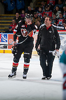 KELOWNA, CANADA - FEBRUARY 28: Travis Sanheim #32 of Calgary Hitmen skates to the bench with the Calgary Hitmen's athletic therapist on February 28, 2015 at Prospera Place in Kelowna, British Columbia, Canada.  (Photo by Marissa Baecker/Shoot the Breeze)  *** Local Caption *** Travis Sanheim;