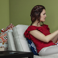 Young caucasian brunette woman using a tablet on the couch. Indoor setting