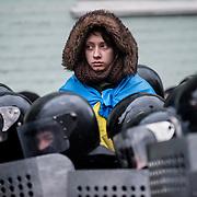 manifestation à Kiev, ukraine le dimanche 8 décembre 2013. une jeune femme portant le drapeau ukrainien se tient a dessus des forces d'intervention.