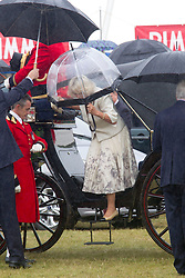 SANDRINGHAM- UK -31-JULY-2013: Britain's Prince Charles, The Prince of Wales and Camilla, The Duchess of Cornwall attend the annual Sandringham Flower SHow in the grounds of Sandringham House in Norfolk. The rain did not put off the crowds who lined their route around the show, at the end of which Prince Charles met Zephr, The Bald Eagle mascot of the Army Air Corps which The Prince is the Colonel-In Chief of.<br /> Photo Ian Jones