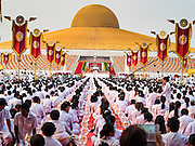 """22 FEBRUARY 2016 - KHLONG LUANG, PATHUM THANI, THAILAND: People pray during the Makha Bucha Day service at Wat Phra Dhammakaya.  Makha Bucha Day is a public holiday in Cambodia, Laos, Myanmar and Thailand. Many people go to the temple to perform merit-making activities on Makha Bucha Day, which marks four important events in Buddhism: 1,250 disciples came to see the Buddha without being summoned, all of them were Arhantas, Enlightened Ones, and all were ordained by the Buddha himself. The Buddha gave those Arhantas the principles of Buddhism, called """"The ovadhapatimokha"""". Those principles are:  1) To cease from all evil, 2) To do what is good, 3) To cleanse one's mind. The Buddha delivered an important sermon on that day which laid down the principles of the Buddhist teachings. In Thailand, this teaching has been dubbed the """"Heart of Buddhism."""" Wat Phra Dhammakaya is the center of the Dhammakaya Movement, a Buddhist sect founded in the 1970s and led by Phra Dhammachayo. The temple is famous for the design of its chedi, which some have likened to a flying saucer or UFO.         PHOTO BY JACK KURTZ"""