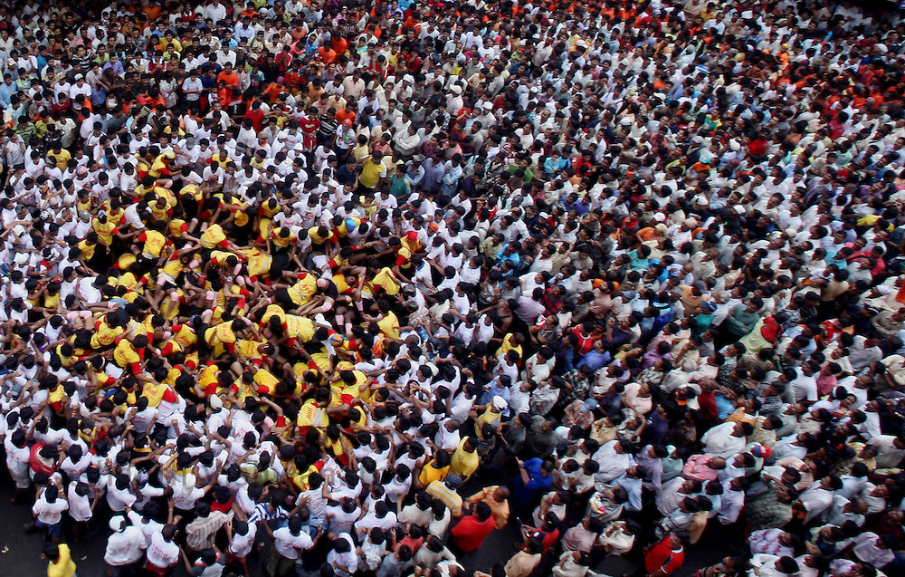 "A pyramind of devotees collapse as they attempt to break a pot containing butter on the occasion of  Krishna Janmashtami (birth of lord Krishna) in Mumbai, September 4, 2007. Janmashtami, which marks the birthday of Hindu god Krishna, will be celebrated across the country on September 4. As legend goes Lord Krishna as a child ate butter kept out of his reach by forming a human pyramid with his friends. Today these ""pots of butter"" contain lakhs of Indian currency as prize money. People form multistoried layers and are ready to risk serious injuries. Photographer: Prashanth Vishwanathan"