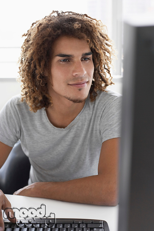 Young man using computer sitting at desk
