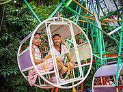 16 NOVEMBER 2013 - BANGKOK, THAILAND: Children ride a Ferris wheel at  Wat Saket during the annual temple fair. Wat Saket is on a man-made hill in the historic section of Bangkok. The temple has golden spire that is 260 feet high which was the highest point in Bangkok for more than 100 years. The temple construction began in the 1800s in the reign of King Rama III and was completed in the reign of King Rama IV. The annual temple fair is held on the 12th lunar month, for nine days around the November full moon. During the fair a red cloth (reminiscent of a monk's robe) is placed around the Golden Mount while the temple grounds hosts Thai traditional theatre, food stalls and traditional shows.    PHOTO BY JACK KURTZ
